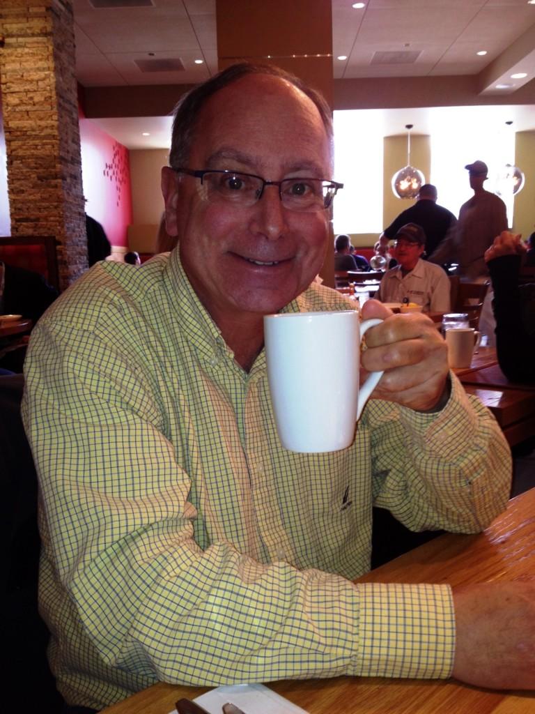 Boston Espresso Dave's Coffee Catering sips cappuccino in a faraway cafe